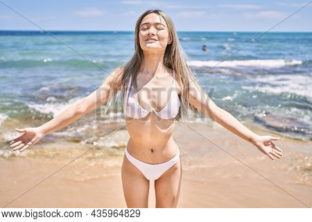 Young chinese girl wearing bikini standing with open arms at the beach.
