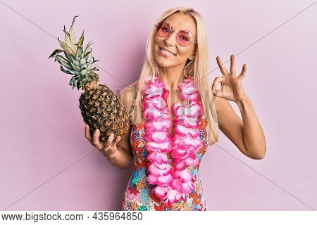 Young blonde woman wearing swimsuit and hawaiian lei holding pineapple doing ok sign with fingers, smiling friendly gesturing excellent symbol