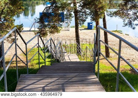 A Wooden Staircase With A Metal Fence Down To The Lake, In A Pine Forest, On A Sunny Day. Nature Is