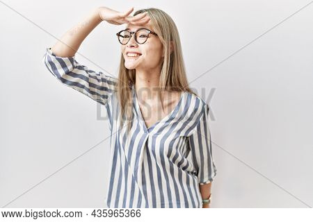 Asian young woman wearing casual clothes and glasses very happy and smiling looking far away with hand over head. searching concept.