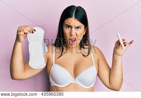 Beautiful brunette woman holding sanitary pad and cotton tampon in shock face, looking skeptical and sarcastic, surprised with open mouth