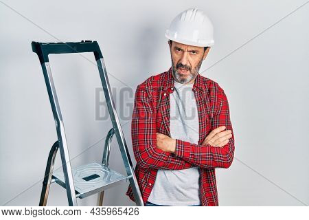 Middle age hispanic worker man with arms crossed gesture using ladder in shock face, looking skeptical and sarcastic, surprised with open mouth