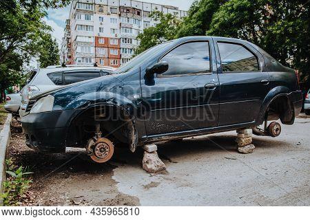 A Broken Passenger Car Without Wheels Stands On Bricks.