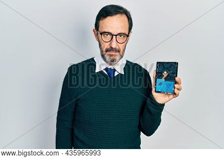 Middle age hispanic man holding hdd disk thinking attitude and sober expression looking self confident