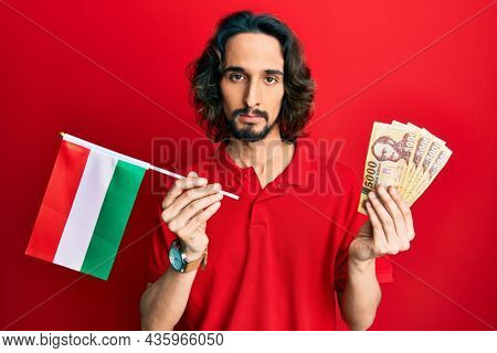 Young hispanic man holding hungary flag and forints relaxed with serious expression on face. simple and natural looking at the camera.