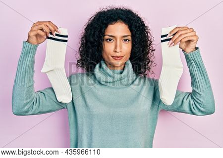 Young latin girl holding socks relaxed with serious expression on face. simple and natural looking at the camera.