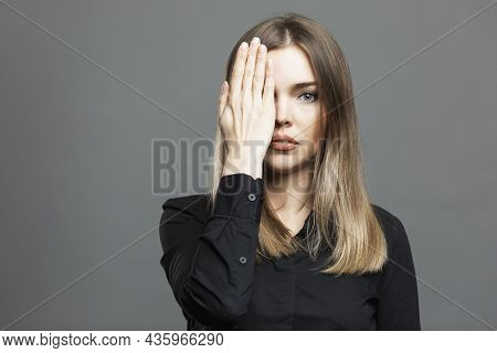 The Young Woman Covered One Eye With Her Hand. Beautiful Blonde In A Black Shirt. Conspiracy Theory