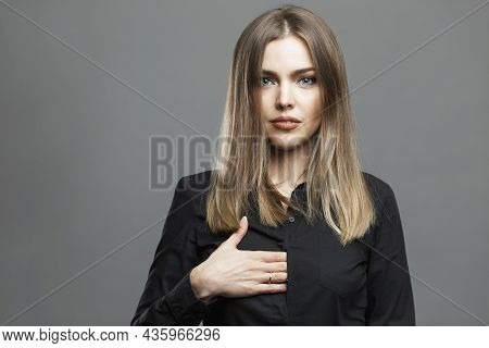 Young Woman Shows A Hidden Hand Sign. Beautiful Blonde In A Black Shirt. Masonic Symbolism And The T