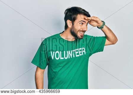 Young hispanic man wearing volunteer t shirt very happy and smiling looking far away with hand over head. searching concept.