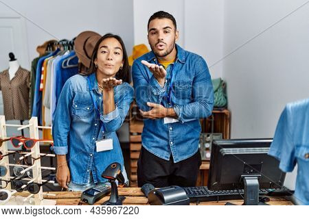 Young interracial people working at retail boutique looking at the camera blowing a kiss with hand on air being lovely and sexy. love expression.