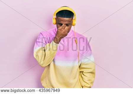 Young black man listening to music wearing headphones tired rubbing nose and eyes feeling fatigue and headache. stress and frustration concept.