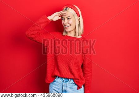 Beautiful blonde woman wearing casual red sweater very happy and smiling looking far away with hand over head. searching concept.