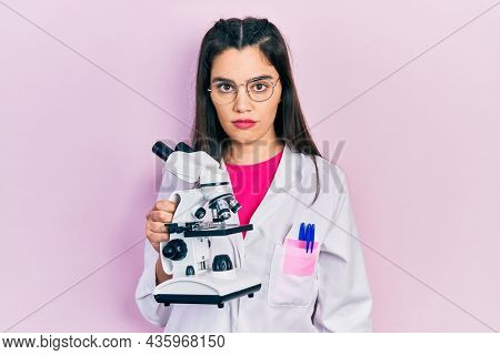 Young hispanic girl wearing scientist uniform holding microscope thinking attitude and sober expression looking self confident