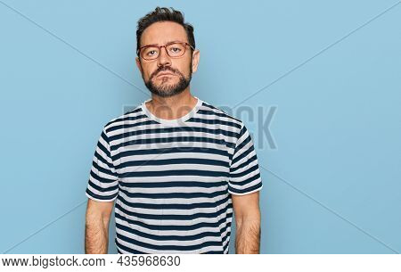 Middle age man wearing casual clothes and glasses relaxed with serious expression on face. simple and natural looking at the camera.