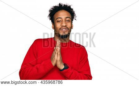 Young african american man with beard wearing casual winter sweater praying with hands together asking for forgiveness smiling confident.