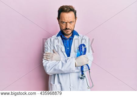 Middle age man wearing doctor uniform skeptic and nervous, frowning upset because of problem. negative person.