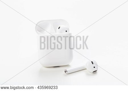 Modern Wireless Bluetooth Earphones With Charging Case On A Light Gray Background. The Concept Of Mo