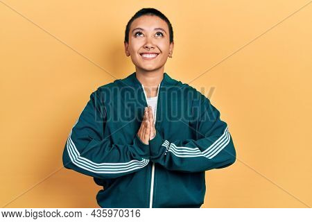 Beautiful hispanic woman with short hair wearing sporty jacket begging and praying with hands together with hope expression on face very emotional and worried. begging.
