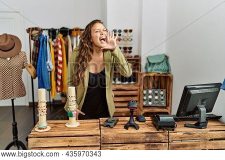 Beautiful hispanic woman working at fashion shop shouting and screaming loud to side with hand on mouth. communication concept.