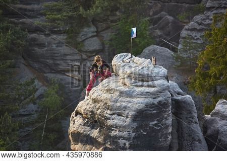 Prachov, Czechia - Circa 2016: Rock climber arriving to the top of a rock tower at Prachov Rocks, popular outdoor destination in Chesky Raj