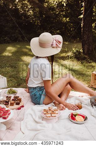 Portrait Photo Of Woman Sitting On The Blanket With Cakes, Sweets And Other Food In Nature - Picnic