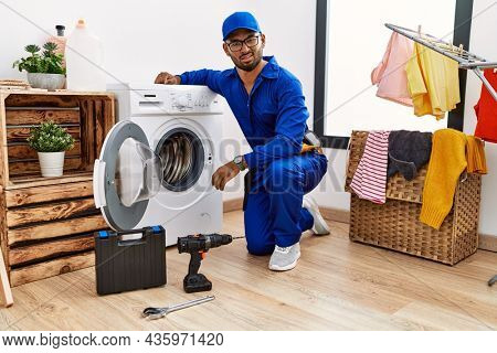 Young indian technician working on washing machine in shock face, looking skeptical and sarcastic, surprised with open mouth