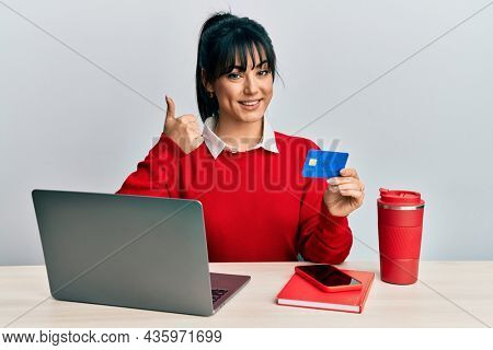 Young brunette woman with bangs working at the office using laptop and credit card smiling happy and positive, thumb up doing excellent and approval sign