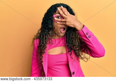 Young latin woman wearing business style and glasses peeking in shock covering face and eyes with hand, looking through fingers afraid
