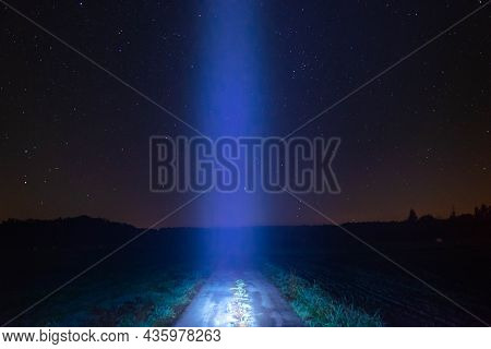 Cloudless Starry Sky Over The Plain. A Dirt Road Runs In The Middle. A Trail Of Light Runs Down The