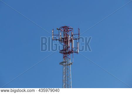 Mast, Base Station For Mobile Telephony. The Metal Structure Is Painted White And Red. A Crown With