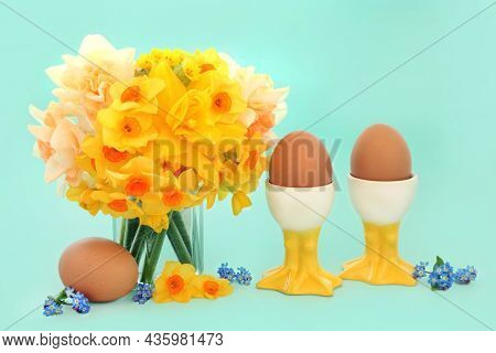 Symbols of spring and Easter with healthy organic brown eggs in novelty egg cups with daffodil, narcissus, cowslip flowers and loose forget me nots. Springtime and Easter concept on pastel turquoise.