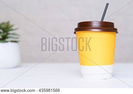 A Yellow Paper Disposable Takeout Coffee Cup With A Brown Cap, And A Straw On White Office Table Wit