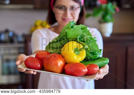 Close-up Of A Plate With Tomatoes, Cucumbers, Paprika And Lettuce In The Hands Of A Woman
