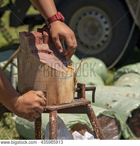 The Hands Of A Wood Chopper Wearing A Red Watch Unscrewing His Timber Log After His Competition Even