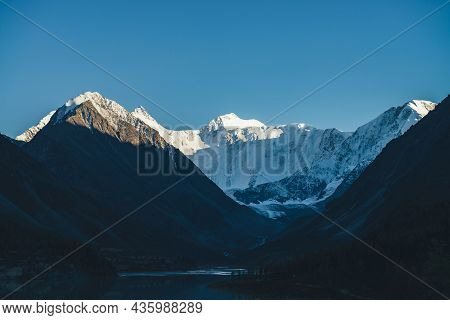 Awesome Alpine Landscape With Mountains Silhouettes And Snow-covered Mountain Tops In Gold Sunshine