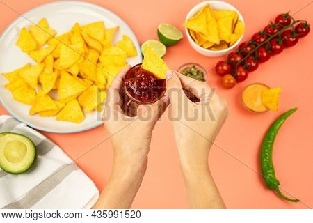 Hands Dipping Nachos In Tomato Salsa Against The Background Of Mexican Food And Vegetables.