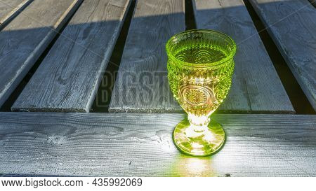 Illuminated Empty Glasses Of Green Glass On A Stem On A Wooden Background. Close-up View. Space For