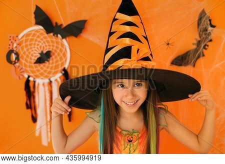 The Girl Makes A Grimace With Her Eyes And Laughing On An Orange Studio Background With Halloween De