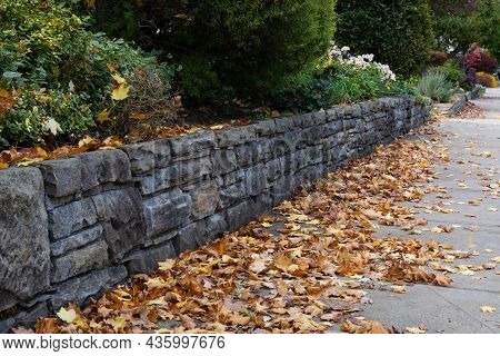 Well Maintained Rusticated Stone Retaining Wall Beside A Sidewalk, Yellow And Brown Autumn Leaf Litt