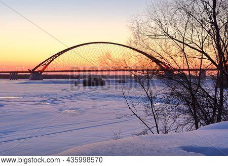 Winter Sunrise On The Ob River. Bugrinsky Automobile Bridge On The Frozen Snow Bank In Novosibirsk