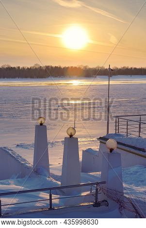 Winter Embankment At Sunset. The Parapet Of The Stairs With Lighting Poles, The Beach Is Covered Wit