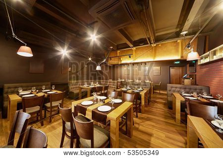 Interior of room in restaurant with wooden furniture and walls of red bricks