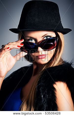 Close-up portrait of a fashionable model in sunglasses and hat.