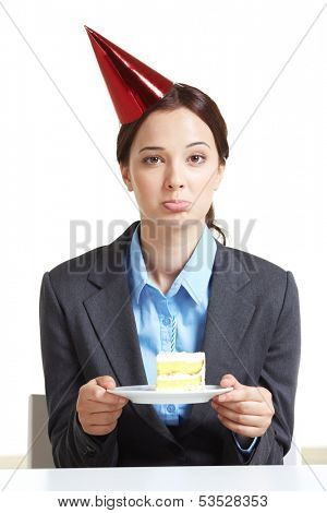 Portrait of young businesswoman in birthday cap holding piece of cake on saucer and looking at camera