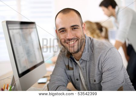 Cheerful guy sitting in front of desktop computer poster