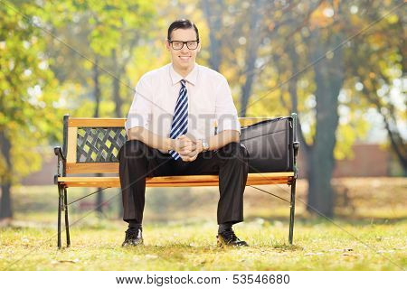 Smiling young businessman sitting on a wooden bench in a park on a sunny day