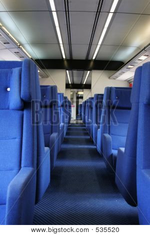 Ground View Of Vacant Seats Inside A Train During Evening Hours.