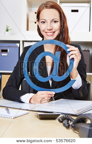 Smiling business woman with a blue internet sign in the office
