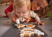 Baby Helping Mother Decorate Homemade Christmas Cookies With Glaze