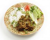 "Lamb or ""gosht"" dry fried curry in the Pakistani or north Indian style, served with basmati rice garnished with coriander leaves, and a lettuce and tomato salad. poster"